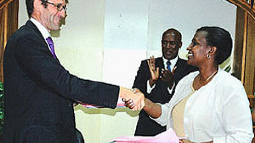 Ambassador Roux (left) shakes hands with Museminari after signing the agreements as Wellas Mukama, the in - charge of the Europe desk, applauds. This was at offices of the Foreign Affairs ministry. (Photo/ G. Barya)