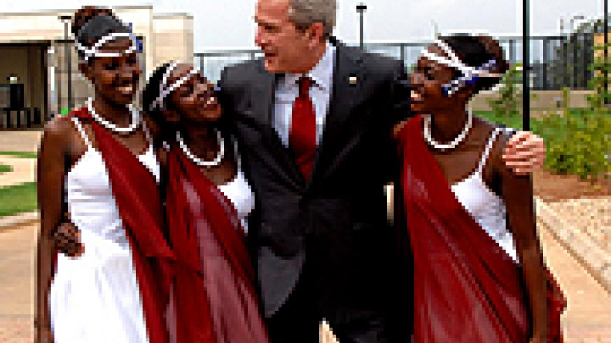 ABOVE: Bush poses for a photo with Rwandan traditional dancers at the US Embassy offices