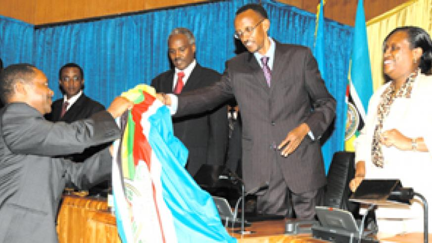 President Kagame hands over the EAC flag to Dr Anastase Shyaka, while L-R, Senate President Dr Vincent Biruta, Dr Murigande and Ms Beatrice Kiraso look on. This was after the launch of nationwide consultations on the EA Political Federation at Parliament