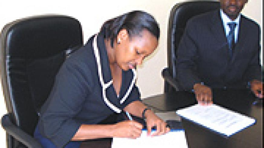 Linda Bihire the new infrastructure minister signing instruments of power allowing her to be the political head of the ministry as Ambassador Kamanzi, former head of the ministry looks on. (Courtesy photo).