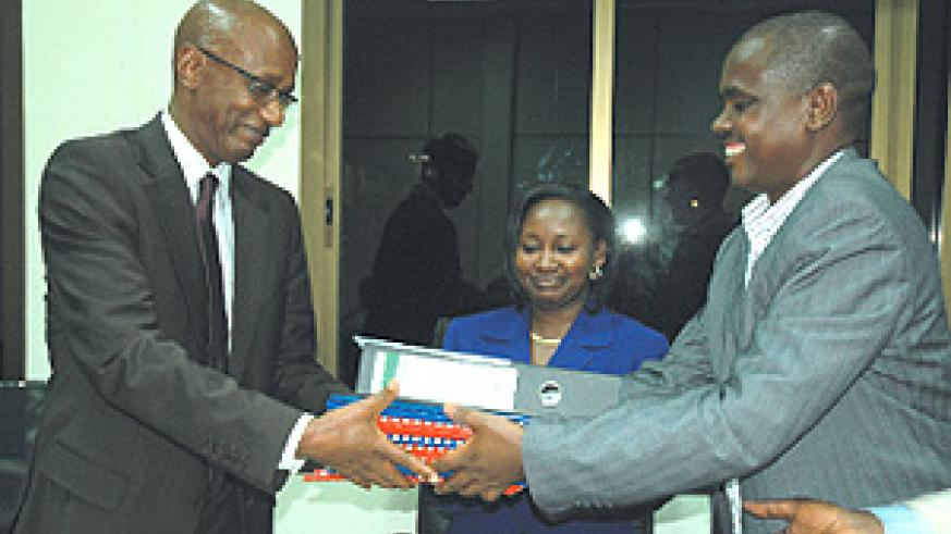The outgoing board chairman of HIDA Barnabé Sebagabo (R) handing over all the documents to the new board Chairman David Himbara at Hida offices yesterday. (Photo/ G.Barya)