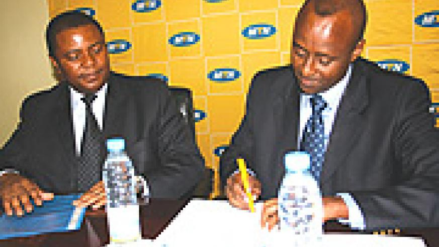 Ferwafa boss, Brig. Gen. Jean Bosco Kazura signs the agreement as MTN Rwanda Chief Executive Officer Themba Khumalo looks on.