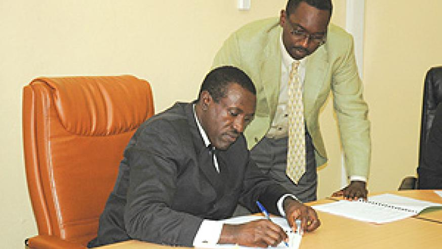 Health Minister Jean-Damascène Ntawukuliryayo signs while Global Fund Country coordinator Daniel Ngamije looks on. (Photo/ Mbanda John).