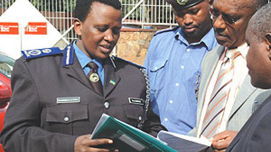 Commissioner General of Police Mary Gahonzire (L) and her Burundian counterpart Fabien Ndayishimiye (2nd right) read through road safety regulations on Tuesday while Traffic Police Commander Robert Niyonshuti (C) looks on. This was during the launch of th