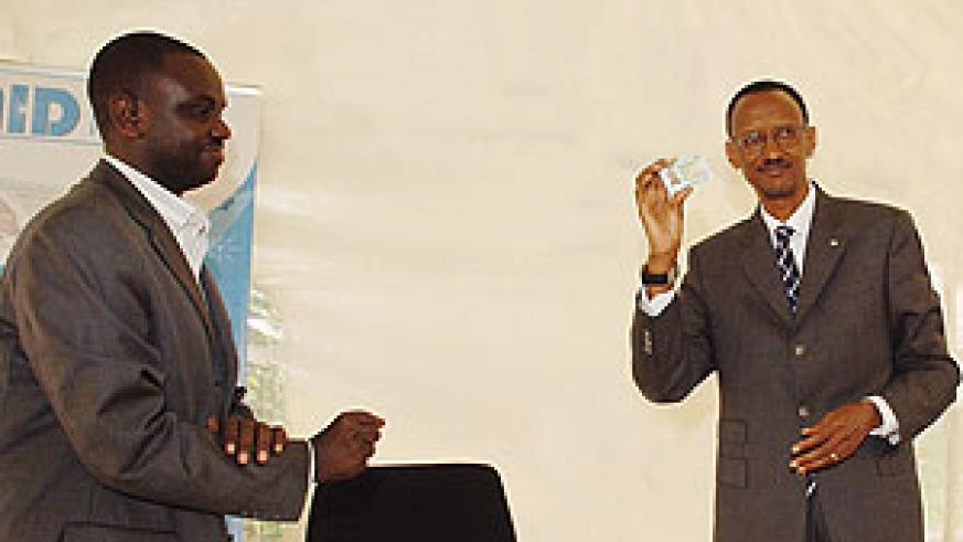 I HAVE GOT MINE, GO GET YOURS: President Paul Kagame (R) displays his National ID shortly after launching the National ID distribution process yesterday. (Photo/ G. Barya)