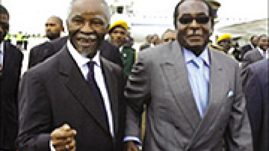 South African president Thabo Mbeki hand in hand with Zimbabwe's Robert Mugabe.