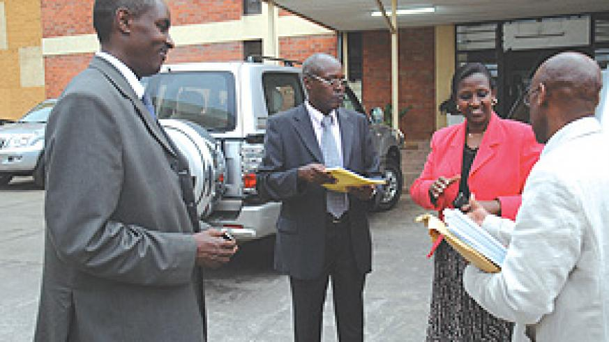 Jean de Dieu Mucyo (L), who chaired the inquiry into the role of the French in the Genocide, with other members of the commission, hands over the report to the Minister of Foreign Affairs, Rosemary Museminari, outside the Ministry of Justice buildings.(Ph