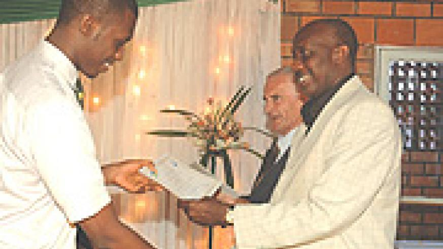 The Chairman Board of Directors Riviera High School, Charles Karake, hands over a certificate to a student. (Photo/ G.Barya).