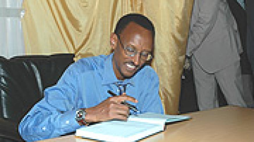 President Paul Kagame signs a visitor's at Gikondo Expo Grounds in Kigali in 2006. The President is expected to open exhibion. (File photo).