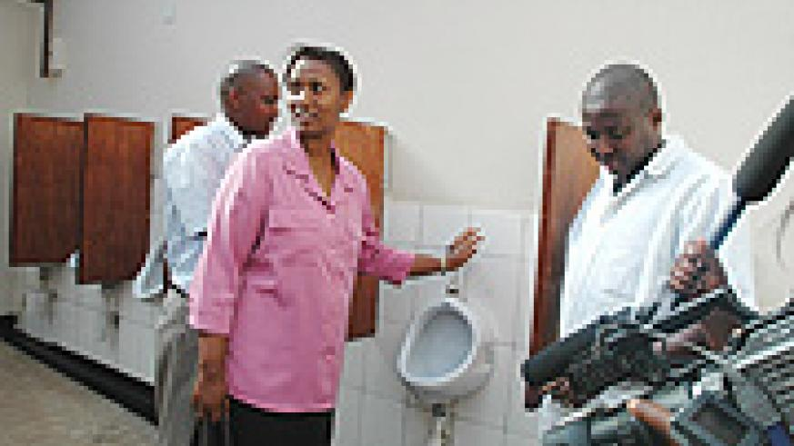 ENVIROMENTALLY FRIENDLY: KCC's in charge of Social Affairs, Jeanne d'Arc Gakuba (C) shows the media and public the inside of the Eco-toilet. (Photo G.Barya).