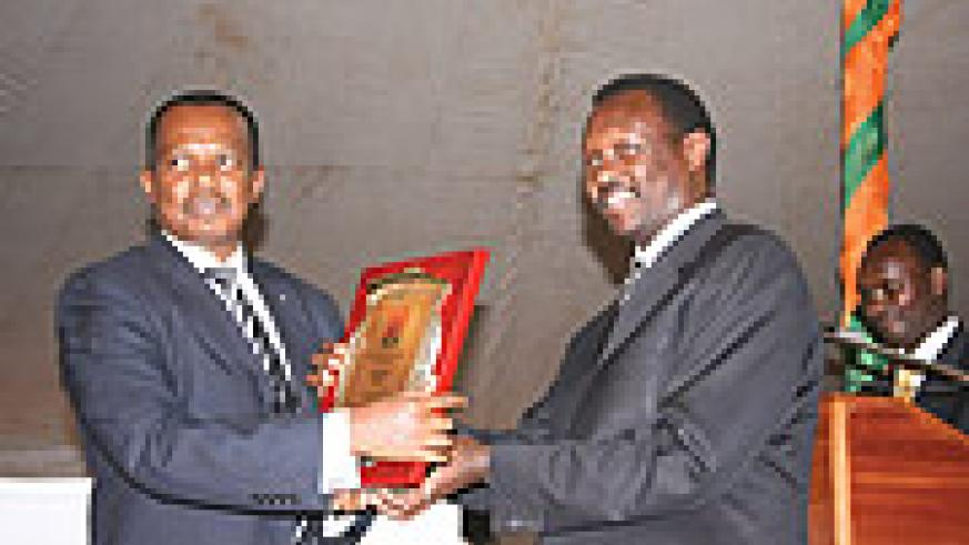 Vincent Karega, State Minister for Industry and Investment Promotion (L) receiving a trophy from Robert Bayigamba, President of the Private Sector Federation.(Courtesy photos)