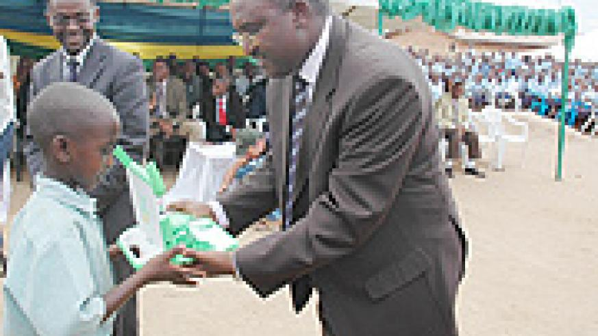 A child receives a Laptop from Minister Mutsindashyaka as Minister Romain Murenzi looks on. (Photo/ J. Mbanda)