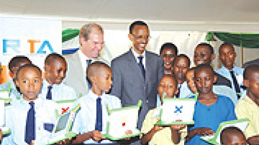 Smart kid: President Kagame watching admiringly as one of the beneficiaries of the One Laptop Per Child project shows off his skills. (File photo)