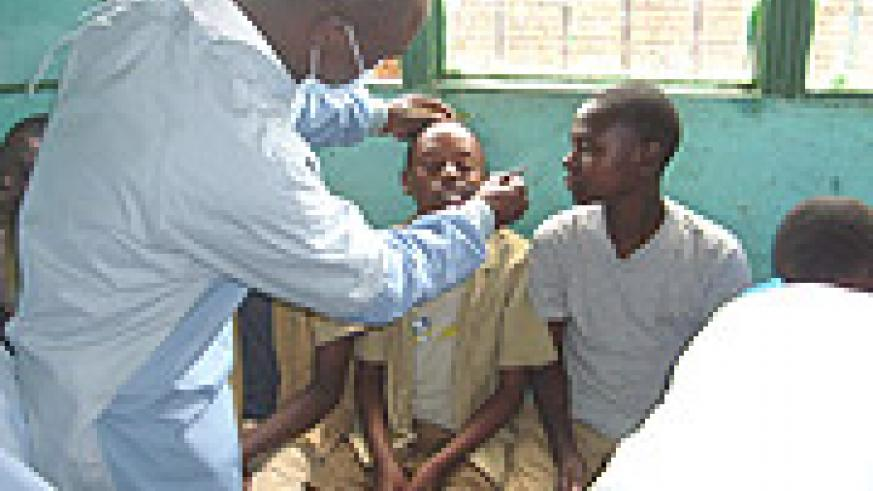 SAY AH: A dentist takes checks a young boy's teeth during the launch or the Oral Health Awareness Week yesterday. (Courtesy Photo).