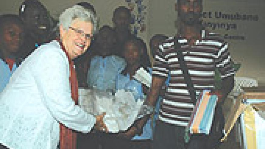 Jill Fenton the Executive  Director of Green Hills Academy hands over the donations to the Kinyinya orphans. (Photo/ G.Barya).