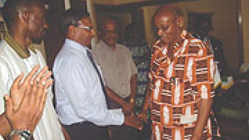 Former Kigali-Virunga Rotary president, James Vuningoma (R) welcoming a new member.(File photo)