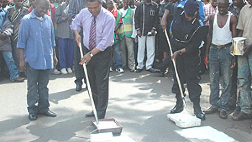 The acting Commissioner General of Police, Mary Gahonzire, with MTN CEO,  Themba Khumalo, painting a Zebra crossing to launch the traffic safety week  yesterday. (Photo/ G. Barya).