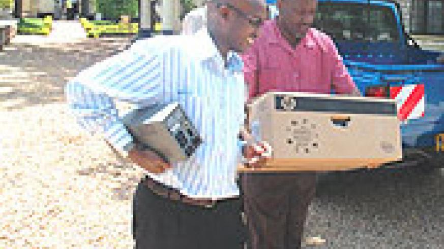The Director of SOS Children Village Alfred Munyantwali (L) carries away his computer. (Photo/ J Mbanda)