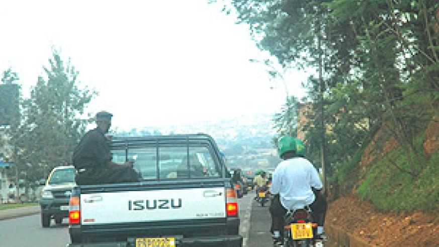 FLOUNTING THE LAW IN FULL VIEW OF THE LAW: Motorcyclists carrying passengers overtake a Police car on the wrong side of the road and get away with it. (Photo/ J. Mbanda).