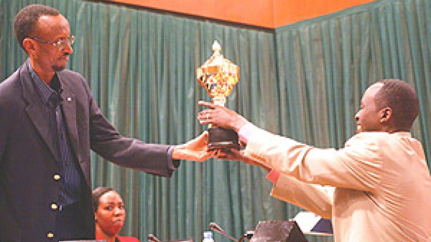 President Paul Kagame giving a trophy to Nyamagabe mayor Alphonse Munyantwari after his district emerged the best in implementing performance contracts. (Photo/G.Barya).