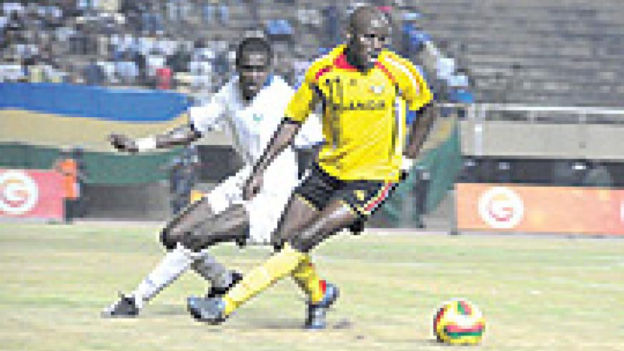 Uganda's Egyptian based professional Geoffrey Massa tries to dribble past a Rwanda's Alou Gasueka. Uganda will play Kenya in the 2009 Cecafa senior finals (Photo / A. E. ORYADA)
