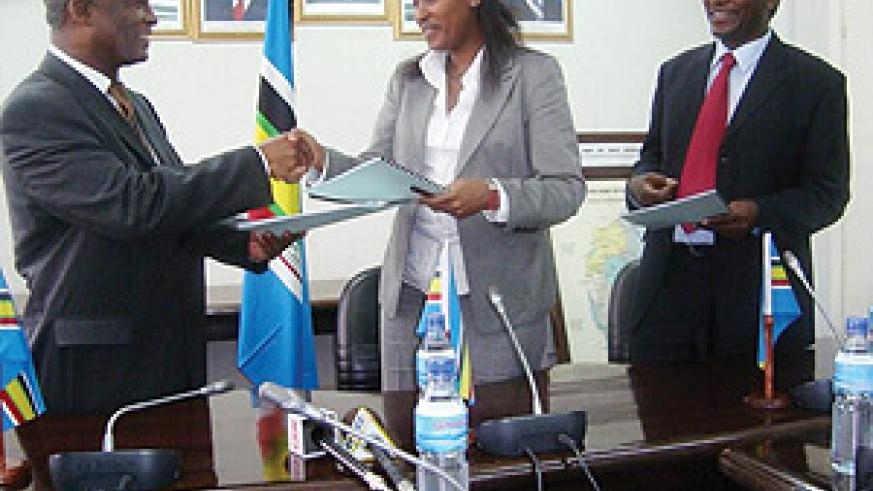 Linda Bihire (centre),  Dr. Shukuru Jumanne Kawambwa (left) and Philippe Njoni (right) exchange the signed MoU in Arusha, Tanzania. (Courtsey Photo)