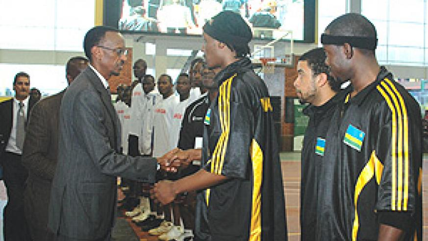 President Kagame shakes hands with National Basketball Team skipper, Hamza Ruhezamihigo, at Rwanda men's opening game of the Fiba Africa Zone V qualifiers that got underway yesterday. Rwanda beat  Uganda 93-68. (Photo/ G. Barya).
