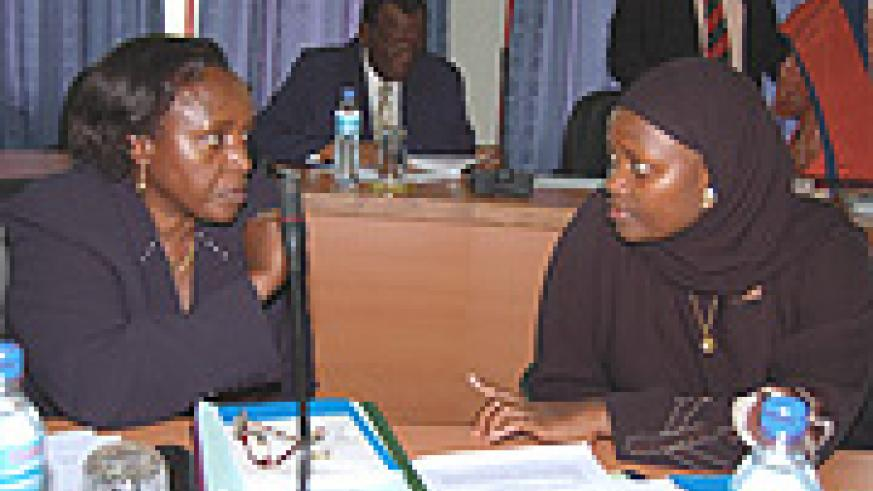 MP Nusura Tiperu (right) talks to MP Odette Nyiramirimo of Rwanda during an EALA session recently.