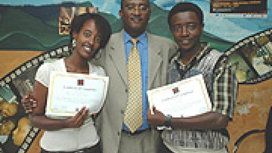 Some of the graduands in at the Film Institute, Tega Mutimura (L) and Yves Gahinde pose for a photo with Minister Mutsindashyaka after their graduation. (Courtsey Photo).