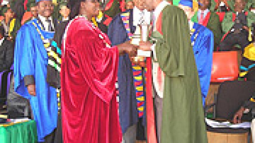 Professor Faustin Rutembesa recieves recognition from Minister Gahakwa for his distinguished service to the University. (Photo P. Ntambara).