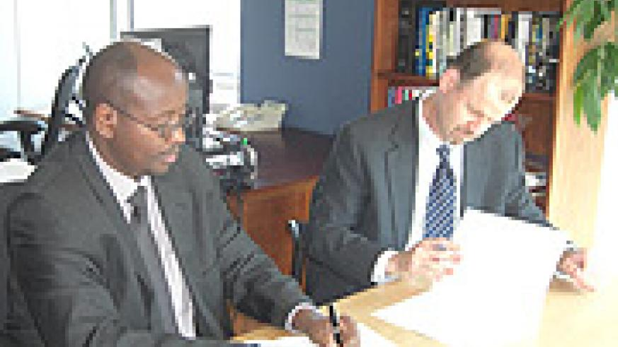 Finance Minister James Musoni and the WB country director, Johannes Zutt signing the agreement in Washington. (Courtesy photo).
