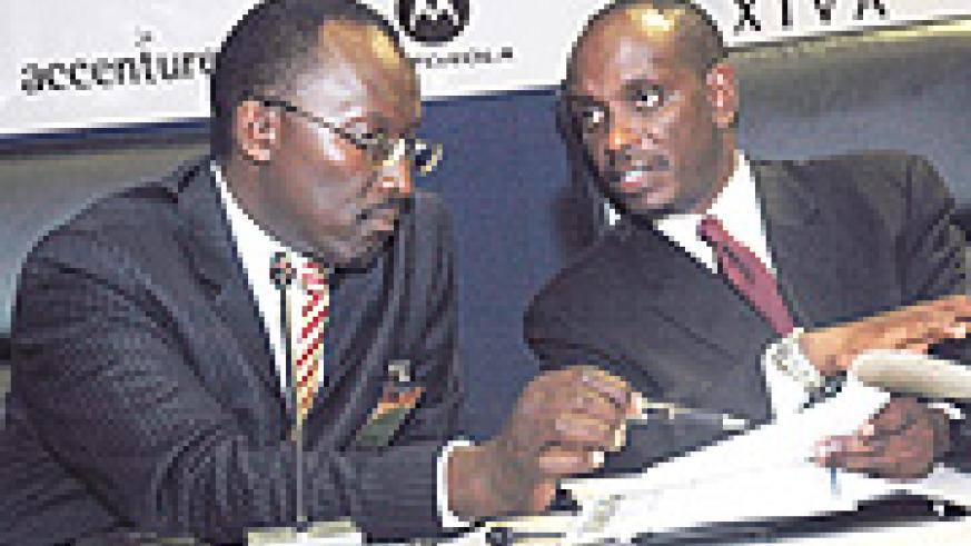 Health Minister Richard Sezibera (R) consults with MTN COO Andrew Rugege during the meeting at Prime Holdings on Thursday. (Photo J Mbanda).