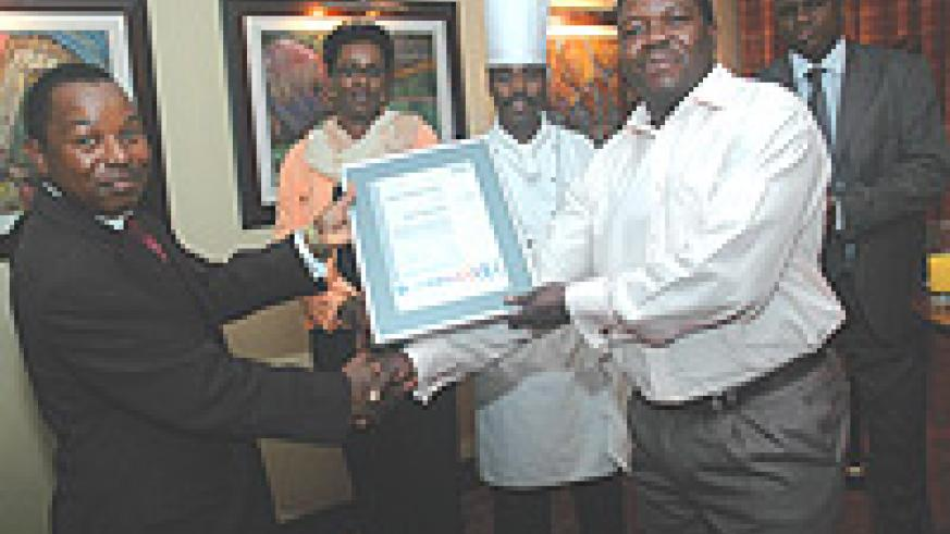 Mugo W. Maringa (L), Kigali Serena Hotel Country Manager receiving a certificate from Ronald Matsiera, the SGS representative.