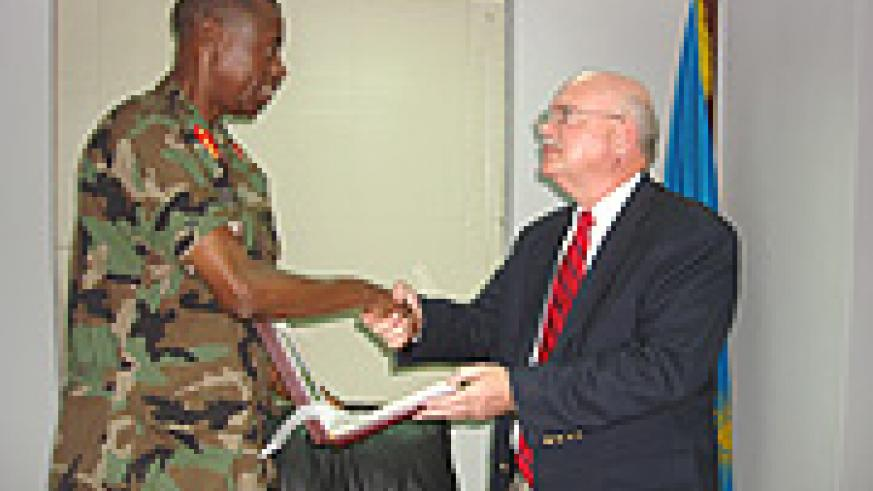 Gen. James Kabarebe hands a gift to William Huntington, after their meeting at the former's office. (Courtsey Photo).
