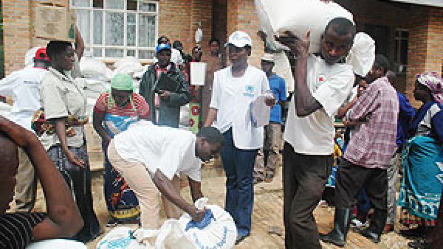 UNHCR and Red Cross staff supervising the distribution of food to returnees from Uganda at the Rwanda Red Cross Headquarters in Gacuriro before they were transported to their respective districts. (Photo / J Mbanda)