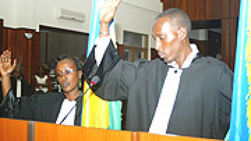 Monique Munyankindi (L) and Frederic Musabwa Kiruhura taking the oath yesterday.(Photo GBarya).