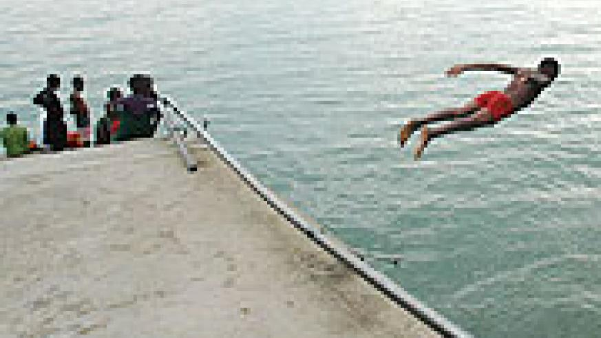 A boy dives into the water while others look on. (File photo)