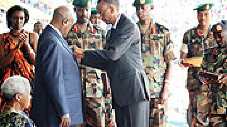Ugandan president Yoweri Museveni being decorated  by his counterpart Paul Kagame on liberation day.