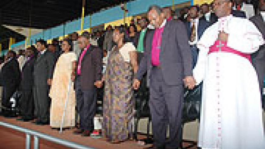 Religious leaders join hands in Prayer during the convention at Amahoro stadium. (Photo J Mbanda)