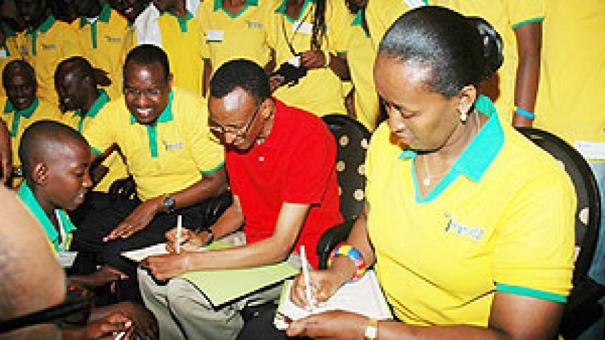 President Paul Kagame and First Lady Jeannette sign autographs for the youth after the meeting. (Photo J Mbanda)