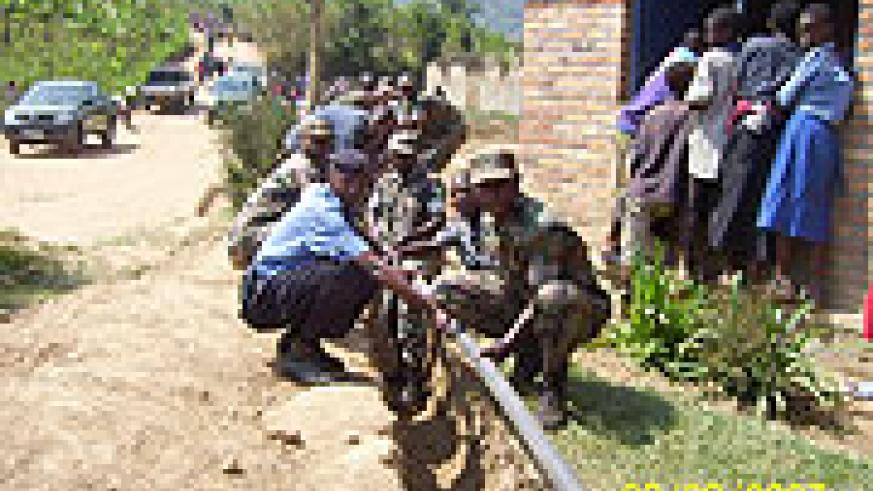 RDF 408 Brigade soldiers and  National Police officers lay down water pipes to provide clean water to residents of Tumba Sector in Rulindo District (Photo A.Gahene).
