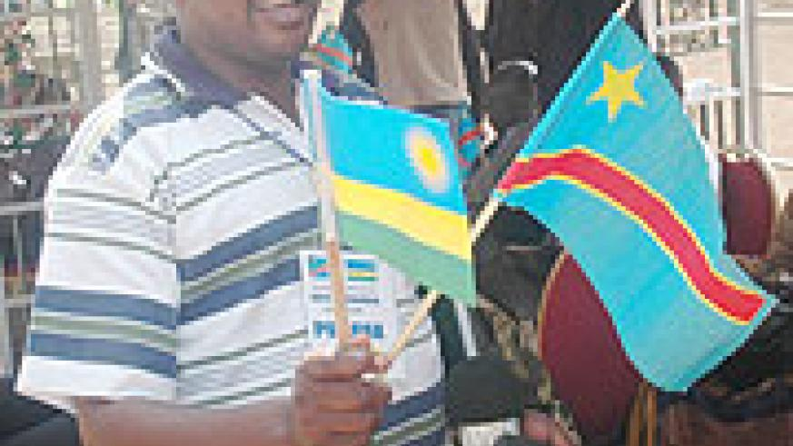 A Congolese journalist admires flags of Rwanda and DRCongo, a sign of the Umoja wetu spirit.