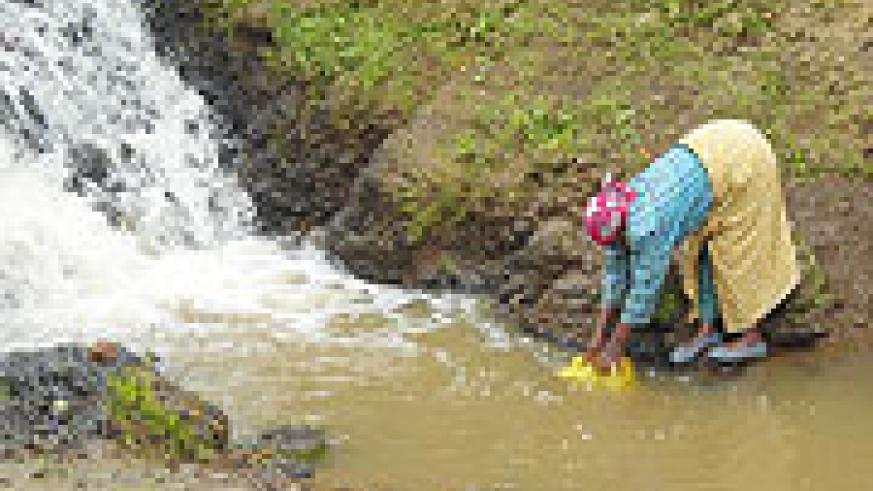 A woman fetches water in one of the water sources  in Ruhengeri.(Photo B Mukombozi).