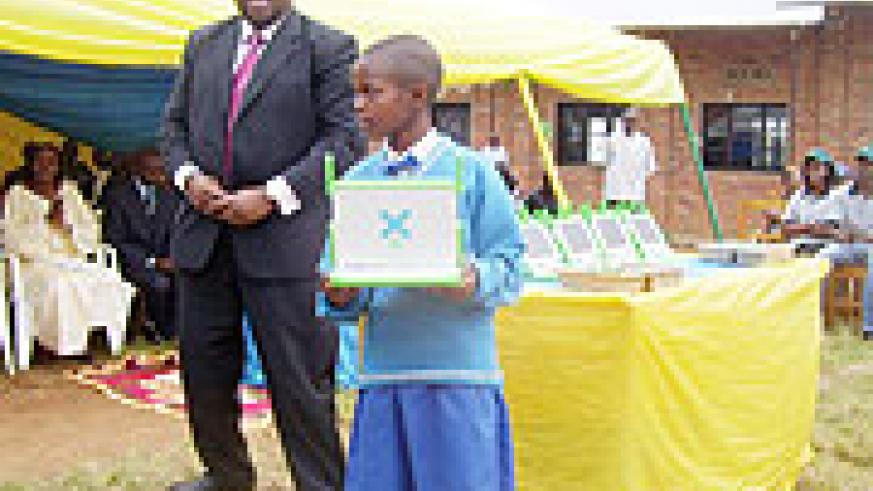 Microsoft Corporation representative David Ochanda gives out a Laptop to one of the best exam performing girls at Inyange Primary School. (Photo: A. Gahene)