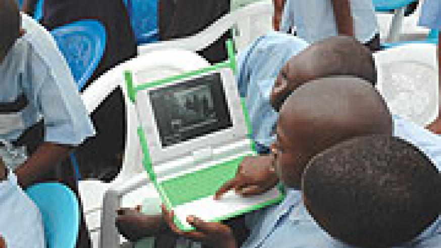 Kagugu Primary School boys try to take photographs with one of the Lap tops given to them. It might take longer for others to receive such laptops
