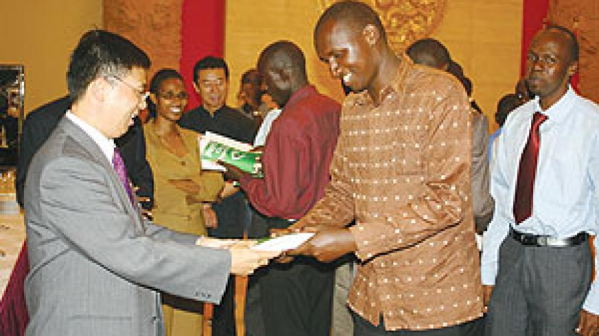 The Charge d'Affaires at the Chinese embassy in Kigali, Li Yigang, hands over a text book to one of the students heading to China for further studies. (Photo/ F. Goodman)