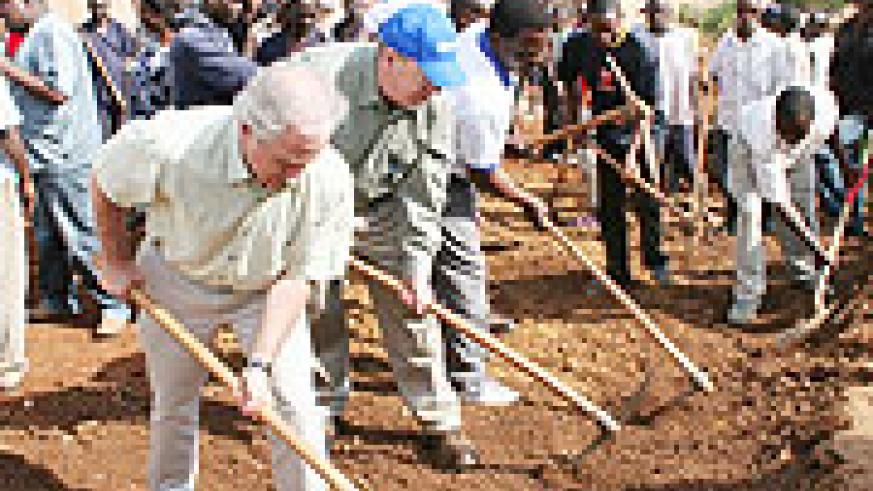 US Senators Johnny Isakson and Bob Corker participate in a road widening project for Umuganda. This kind of community participation is commendable.