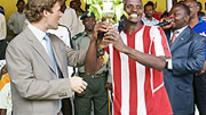 Brwalirwa Managing Director hands over a trophy to Entircelles FC player after the football match (Courtesy Photo).