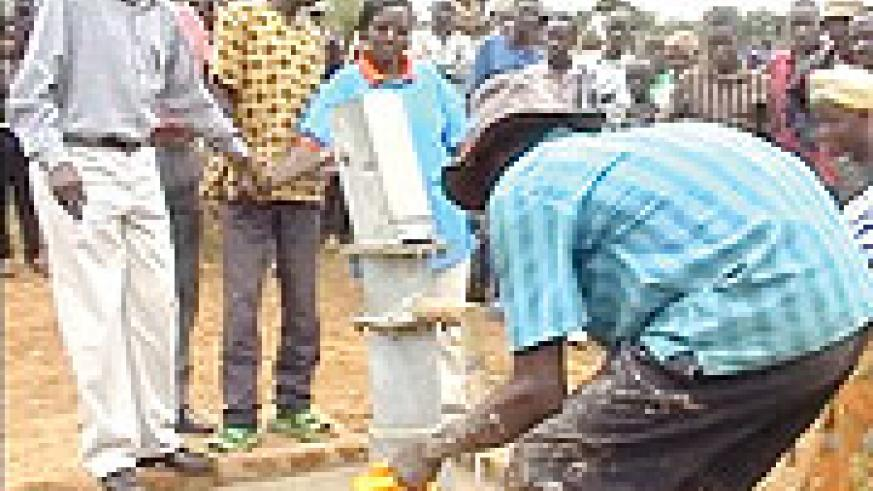 WATER IS LIFE:  Gasagara residents fetch water at the water project's launch, on Saturday.
