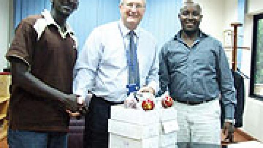 Fina bank's managing director Steve Caley (C) hands over cricket balls and a First-Aid kit to Rwanda Cricket Association (RCA)'s Robert Mugisha (L). On the right is RCA president Charles Haba